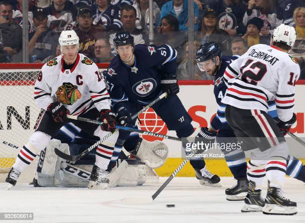Jonathan Toews of the Chicago Blackhawks and Tyler Myers of the Winnipeg Jets look on as Josh Morrissey plays the puck away from the front of the net...