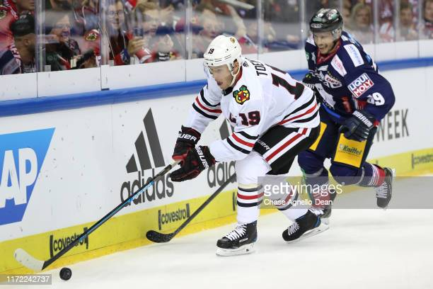 Jonathan Toews of the Chicago Blackhawks approaches the puck ahead of Florian Kettemer of Eisbaren Berlin in the first period during the NHL Global...