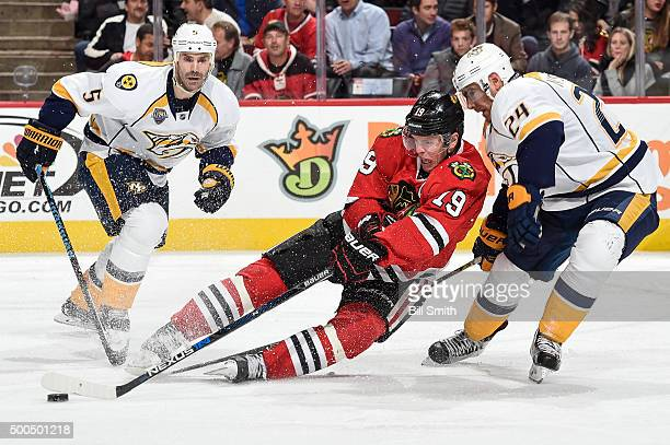 Jonathan Toews of the Chicago Blackhawks attempts to grab the puck against Eric Nystrom and Barret Jackman of the Nashville Predators in the third...