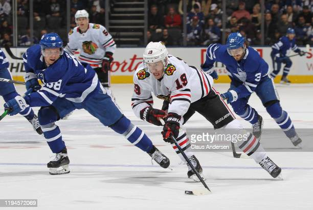 Jonathan Toews of the Chicago Blackhawks breaks between Timothy Liljegren and Rasmus Sandin of the Toronto Maple Leafs during an NHL game at...