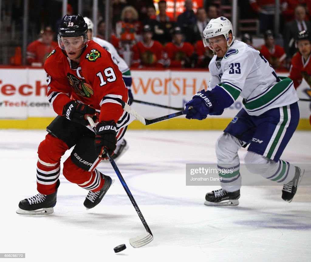 Jonathan Toews #19 of the Chicago Blackhawks breaks up the ice in front of Henrik Sedin #33 of the Vancouver Canucks at the United Center on March 21, 2017 in Chicago, Illinois. The Canucks defeated the Blackhawks 5-4 in overtime.