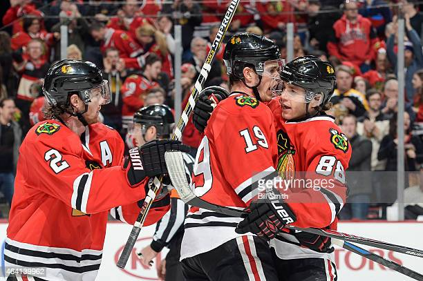 Jonathan Toews of the Chicago Blackhawks celebrates with Duncan Keith and Patrick Kane after scoring against the Boston Bruins in the first period...