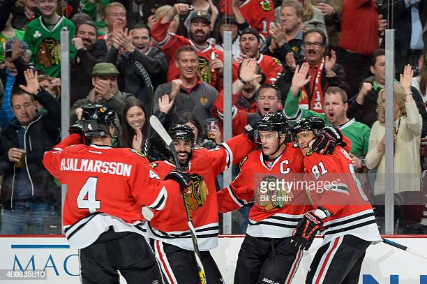 Jonathan Toews of the Chicago Blackhawks celebrates with Niklas Hjalmarsson Johnny Oduya and Marian Hossa after scoring his second goal in the first...