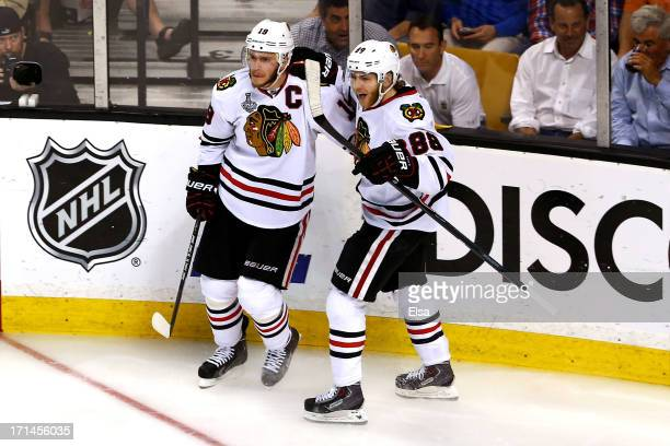 Jonathan Toews of the Chicago Blackhawks celebrates with teammate Patrick Kane after Toews scored a goal in the second period against Tuukka Rask of...