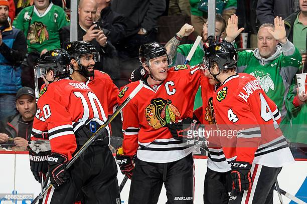 Jonathan Toews of the Chicago Blackhawks celebrates with teammates including Johnny Oduya after scoring his second goal in the first period against...