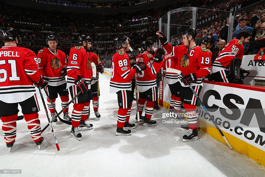 Jonathan Toews #19 of the Chicago Blackhawks (right) celebrates with teammates after the Blackhawks defeated the Carolina Hurricanes 2-1 at the United Center on January 6, 2017 in Chicago, Illinois.