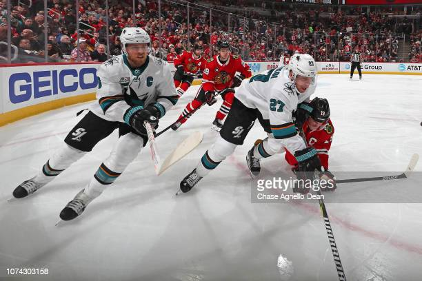 Jonathan Toews of the Chicago Blackhawks chases the puck against Joe Pavelski and Joonas Donskoi of the San Jose Sharks in the third period at the...