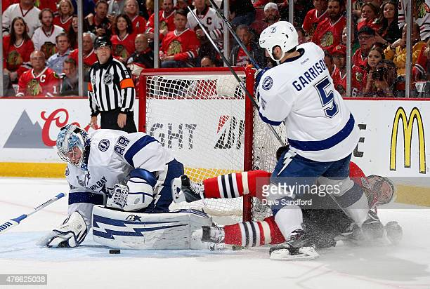 Jonathan Toews of the Chicago Blackhawks collides with Jason Garrison of the Tampa Bay Lightning as goaltender makes a save during the second period...