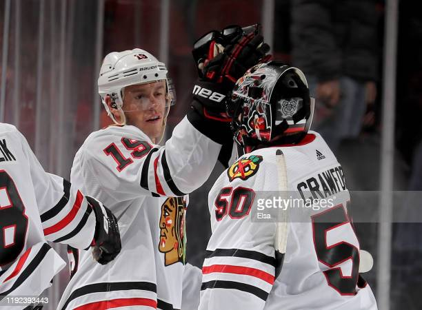 Jonathan Toews of the Chicago Blackhawks congratulates Corey Crawford after the win over the New Jersey Devils at Prudential Center on December 06...