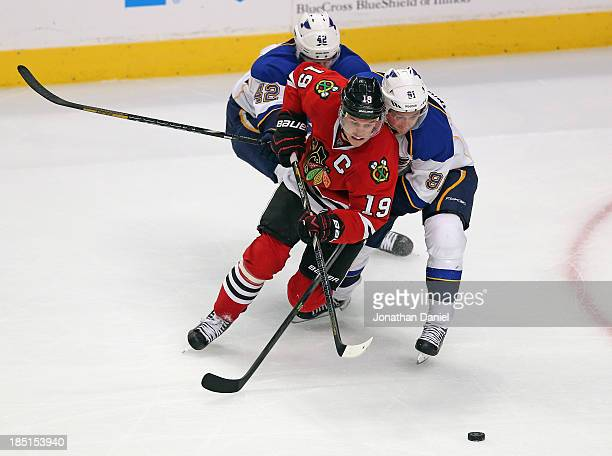 Jonathan Toews of the Chicago Blackhawks controls the puck as he skates between David Backes and Vladimir Tarasenko of the St Louis Blues at the...
