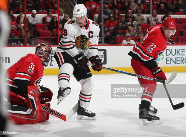 Jonathan Toews of the Chicago Blackhawks creates traffic in front of Scott Darling of the Carolina Hurricanes as teammate Brett Pesce defends during...