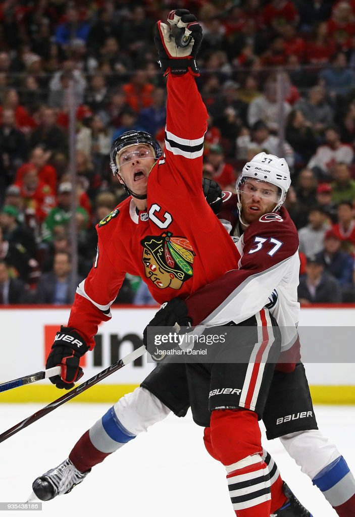 Jonathan Toews #19 of the Chicago Blackhawks ctaches an airborne puck wrapped up by J.T. Compher #37 of the Colorado Avalanche at the United Center on March 20, 2018 in Chicago, Illinois.