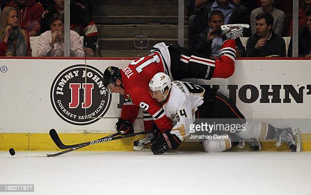 Jonathan Toews of the Chicago Blackhawks falls over Brandon McMillan of the Anaheim Ducks as they battle for the puck at the United Center on October...