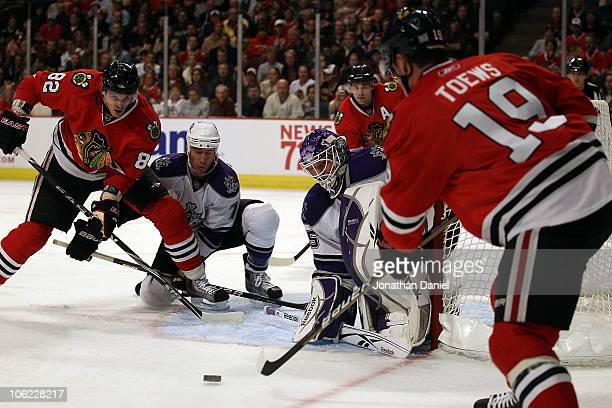 Jonathan Toews of the Chicago Blackhawks fires a shot at Jonathan Bernier and Rob Scuden of the Los Angeles Kings as teammate Tomas Kopecky sets-up...