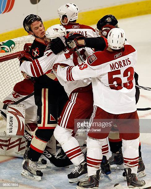 Jonathan Toews of the Chicago Blackhawks gets into a shoving match with Petteri Nokelainen and Derek Morris of the Phoenix Coyotes in front of the...