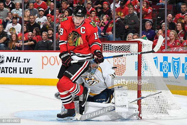 Jonathan Toews of the Chicago Blackhawks gets out of the way of the puck that makes it past goalie Marek Mazanec of the Nashville Predators, for the...