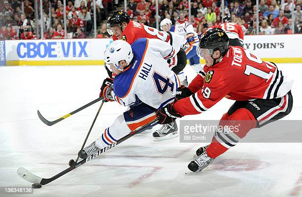 Jonathan Toews of the Chicago Blackhawks grabs the puck as Taylor Hall of the Edmonton Oilers and Marian Hossa of the Blackhawks battle for the puck...