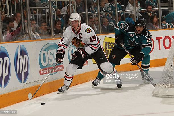 Jonathan Toews of the Chicago Blackhawks handles the puck behind the net away from Manny Malhotra of the San Jose Sharks in Game One of the Western...