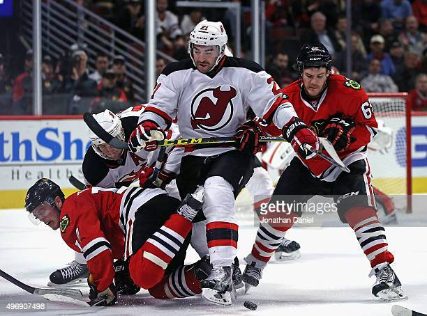 Jonathan Toews of the Chicago Blackhawks hits the ice after a face-off as teammate Andrew Shaw battles with Kyle Palmieri of the New Jersey Devils...