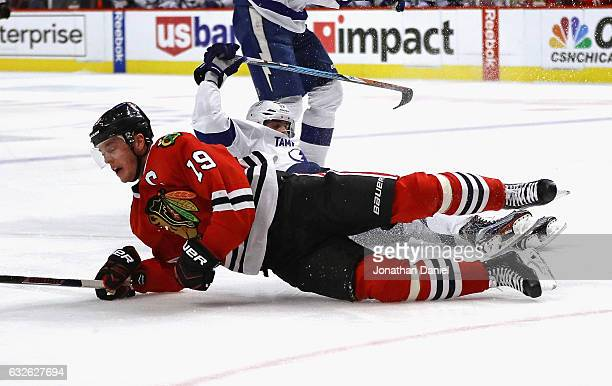 Jonathan Toews of the Chicago Blackhawks hits the ice after being pulled down by Alex Killorn of the Tampa Bay Lightning at the United Center on...