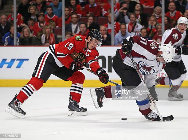 Jonathan Toews of the Chicago Blackhawks hooks Andre Benoit of the Colorado Avalanche for a penalty in overtime at the United Center on January 14...