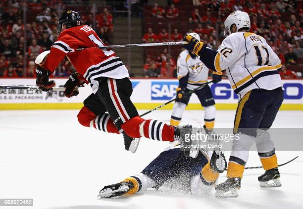 Jonathan Toews of the Chicago Blackhawks hops over PK Subban of the Nashville Predators after shooting as Mike Fisher hooks him with his stick in...