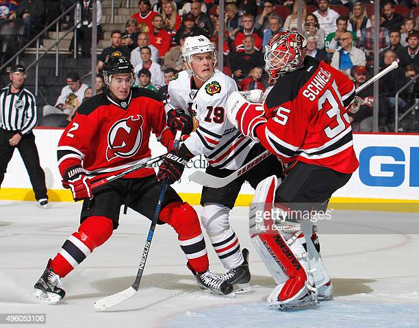 Jonathan Toews of the Chicago Blackhawks is checked by John Moore of the New Jersey Devils as goalie Cory Schneider of the Devils makes a save in the...