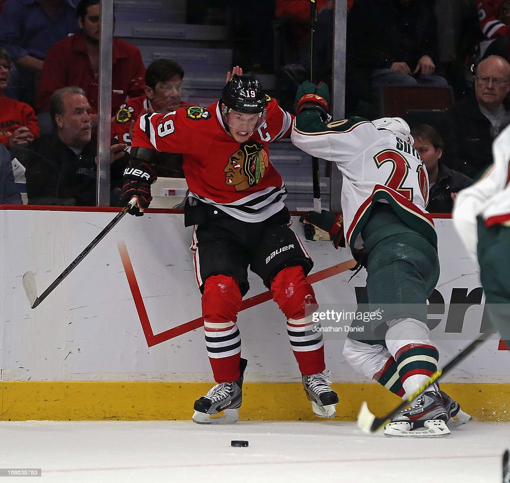 Jonathan Toews #19 of the Chicago Blackhawks is checked by Ryan Suter #20 of the Minnesota Wild in Game Five of the Western Conference Quarterfinals during the 2013 NHL Stanley Cup Playoffs at the United Center on May 9, 2013 in Chicago, Illinois. The Blackhawks defeated the Wild 5-1 to win the series.