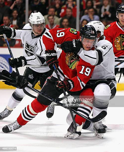 Jonathan Toews of the Chicago Blackhawks is grabbed around the neck by Jake Muzzin of the Los Angeles Kings at the United Center on March 30 2015 in...