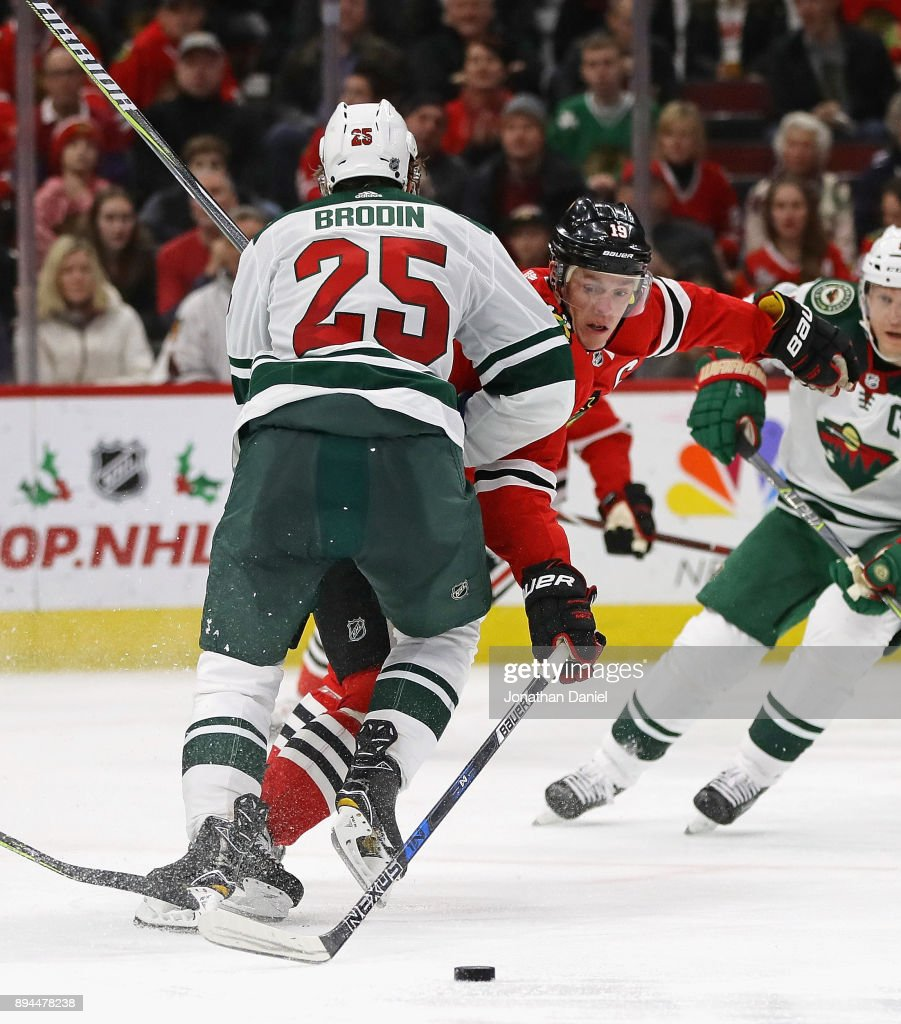 Jonathan Toews #19 of the Chicago Blackhawks is hit by Jonas Brodin #25 of the Minnesota Wild at the United Center on December 17, 2017 in Chicago, Illinois. The Blackhawks defeated the Wild 4-1.