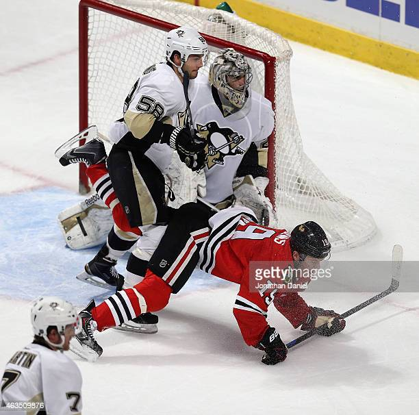 Jonathan Toews of the Chicago Blackhawks is knocked to the ice by Kris Letang of the Pittsburgh Penguins as Marc-Andre Fleury follows the puck at the...