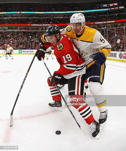Jonathan Toews of the Chicago Blackhawks is pressured by Dan Hamhuis of the Nashville Predators at the United Center on February 21 2020 in Chicago...