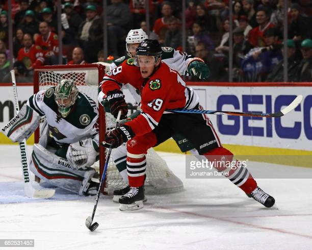 Jonathan Toews of the Chicago Blackhawks is prressured by Jonas Brodin of the Minnesota Wild as he skates around Darcy Kuemper oin the net at the...