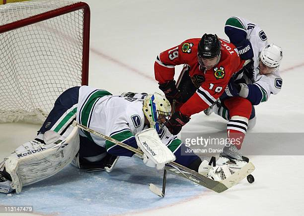 Jonathan Toews of the Chicago Blackhawks is pulled down by Alexandre Burrows of the Vancouver Canucks as Roberto Luongo dives to make the save in...