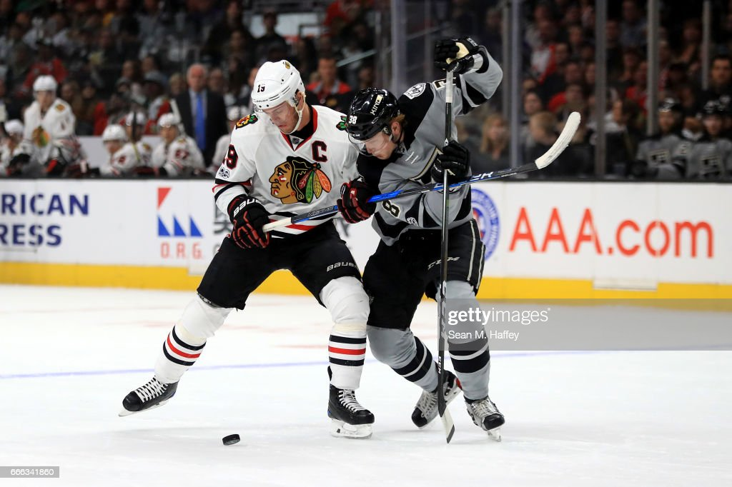 Jonathan Toews #19 of the Chicago Blackhawks is pushed off the puck by Paul LaDue #38 of the Los Angeles Kings during the first period of a game at Staples Center on April 8, 2017 in Los Angeles, California.