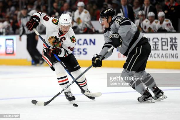 Jonathan Toews of the Chicago Blackhawks is pushed off the puck by Paul LaDue of the Los Angeles Kings during the first period of a game at Staples...