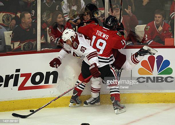 Jonathan Toews of the Chicago Blackhawks pins Derek Morris of the Phoenix Coyotes to the boards as they battle for the puck in Game Four of the...