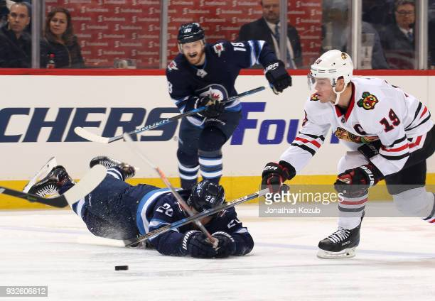 Jonathan Toews of the Chicago Blackhawks plays the puck away from a fallen Blake Wheeler of the Winnipeg Jets during second period action at the Bell...