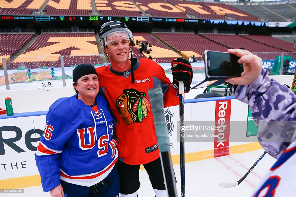 Jonathan Toews #19 of the Chicago Blackhawks poses for a photo with a member of the Wounded Warrior hockey team during practice day for the 2016 Coors Light Stadium Series game against the Minnesota Wild at TCF Bank Stadium on February 20, 2016 in Minneapolis, Minnesota.
