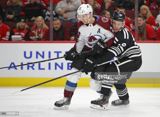 Jonathan Toews of the Chicago Blackhawks pressures Nathan MacKinnon of the Colorado Avalanche at the United Center on November 29 2019 in Chicago...