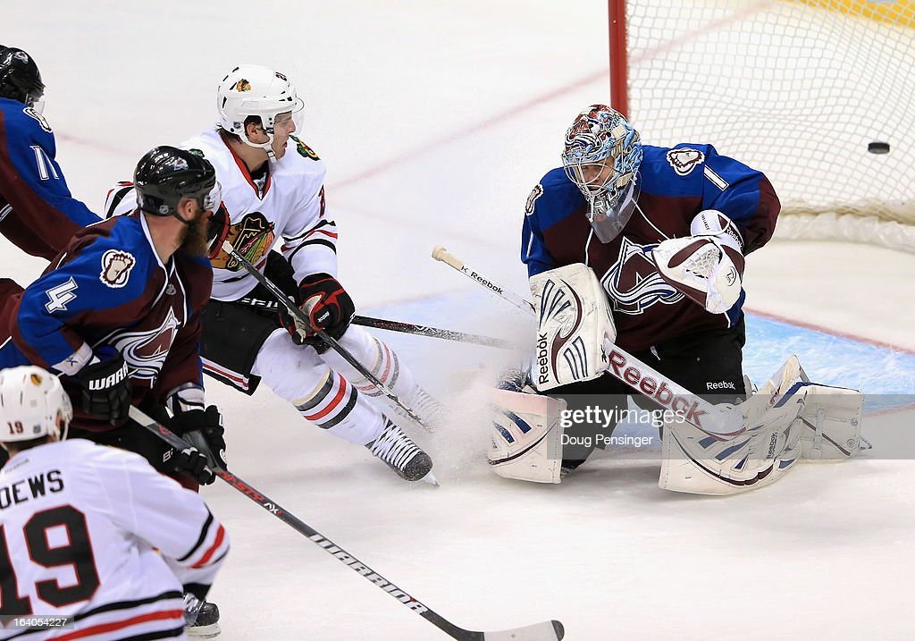 Jonathan Toews #19 of the Chicago Blackhawks puts the puck past goalie Semyon Varlamov #1 of the Colorado Avalanche for a third period goal at the Pepsi Center on March 18, 2013 in Denver, Colorado. The Blackhawks defeated the Avalanche 5-2.