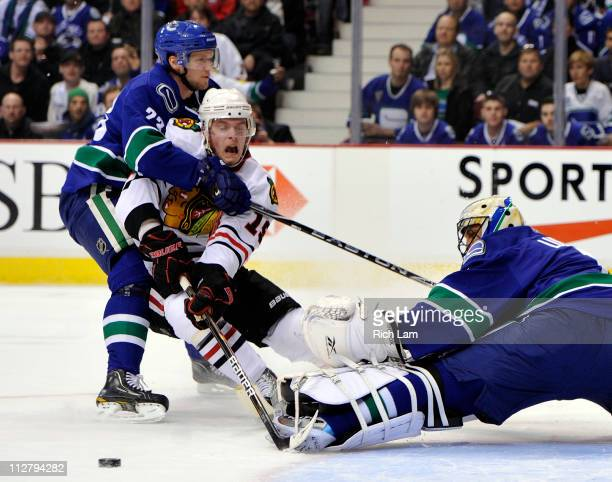 Jonathan Toews of the Chicago Blackhawks reacts while being hauled down by Alexander Edler of the Vancouver Canucks in front of goalie Roberto Luongo...