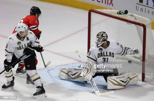 Jonathan Toews of the Chicago Blackhawks scores a first period goal against Stephane Robidas and Richard Bachman of the Dallas Stars at the United...