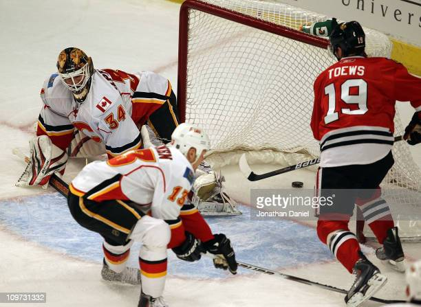 Jonathan Toews of the Chicago Blackhawks scores a goal in the 1st period against Miikka Kiprusoff of the Calgary Flames as Olli Jokinen tries to...