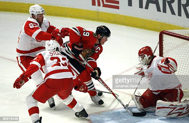 Jonathan Toews of the Chicago Blackhawks scores a goal in the first period against Johan Franzen Brad Stuart and goalie Chris Osgood of the Detroit...