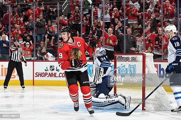Jonathan Toews of the Chicago Blackhawks scores on goalie Michael Hutchinson of the Winnipeg Jets in the third period of the NHL game at the United...