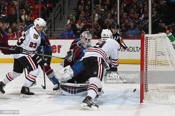Jonathan Toews of the Chicago Blackhawks scores while teammate Kris Versteeg looks on against goaltender Calvin Pickard the Colorado Avalanche at the...