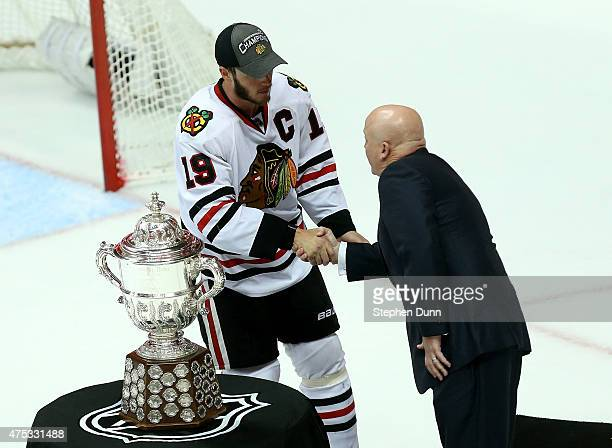 Jonathan Toews of the Chicago Blackhawks shakes hands with NHL Deputy Commissioner Bill Daly as they stand in front of the Clarence S Campbell Bowl...