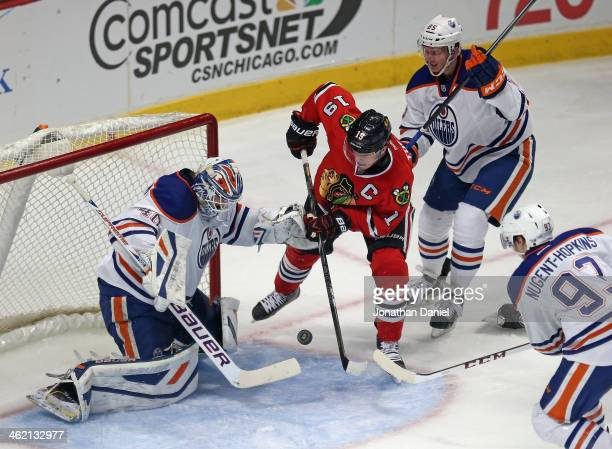 Jonathan Toews of the Chicago Blackhawks shoots against Devan Dubnyk of the Edmonton Oilers as Martin Marincin and Ryan Nugent Hopkins defend at the...