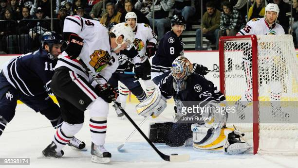 Jonathan Toews of the Chicago Blackhawks shoots the puck against Pekka Rinne of the Nashville Predators as David Legwand defends on December 26 2009...
